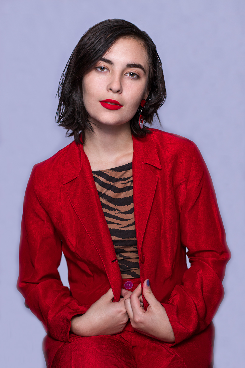 Woman wearing a red suit with red lipstick posed sitting down in front of a white screen.