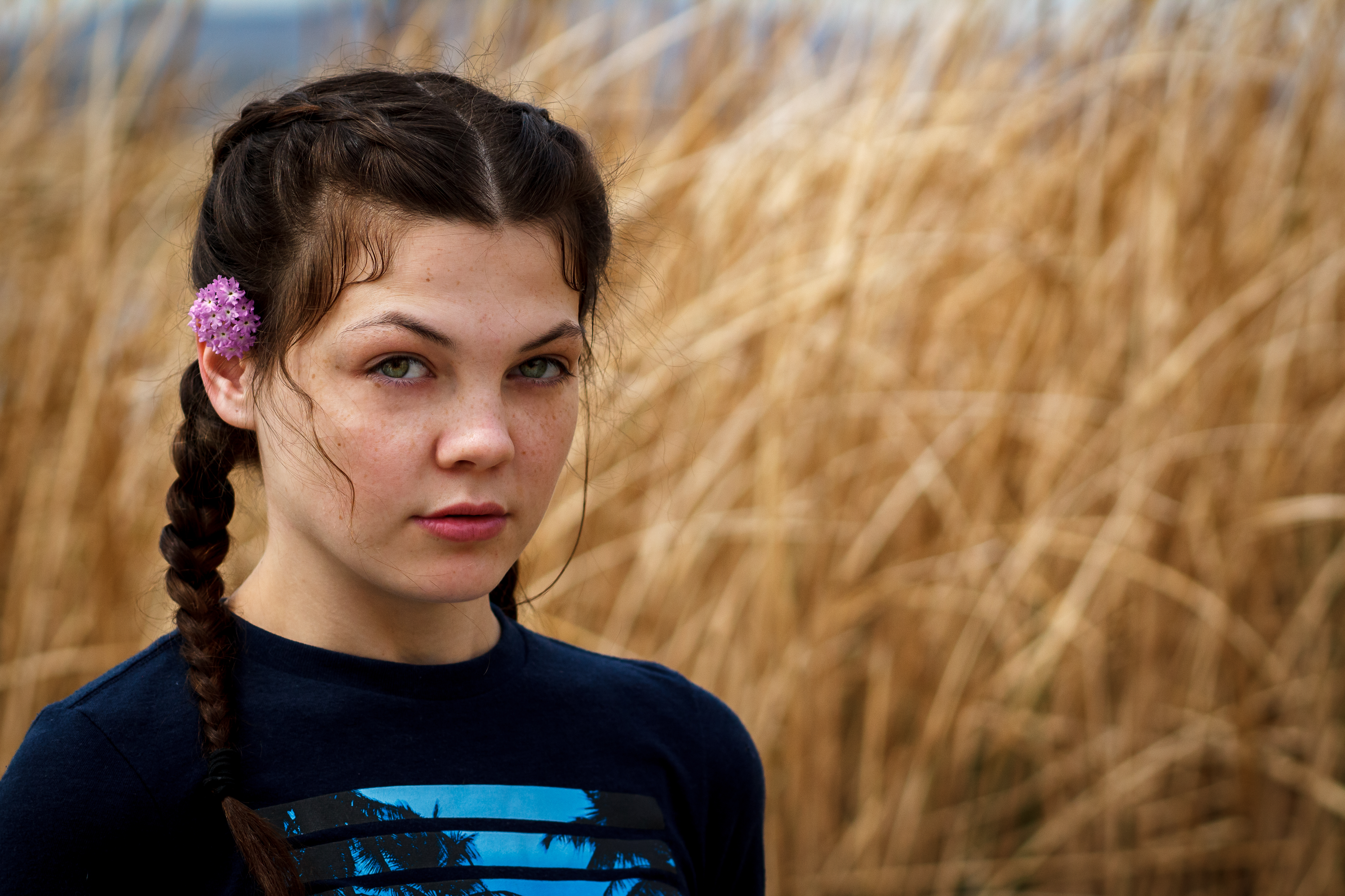 Woman wearing double braids with a flower in her hair posed in front of tall brown grass, with intense expression.